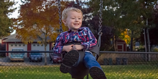 Smiling boy on swing set
