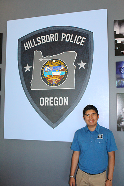 Fernando Aguilar with poster of Hillsboro Police shield