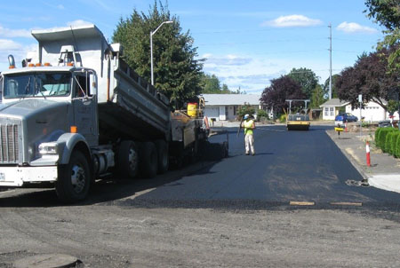 Photo of pavement maintenace crews pouring asphalt onto roadway