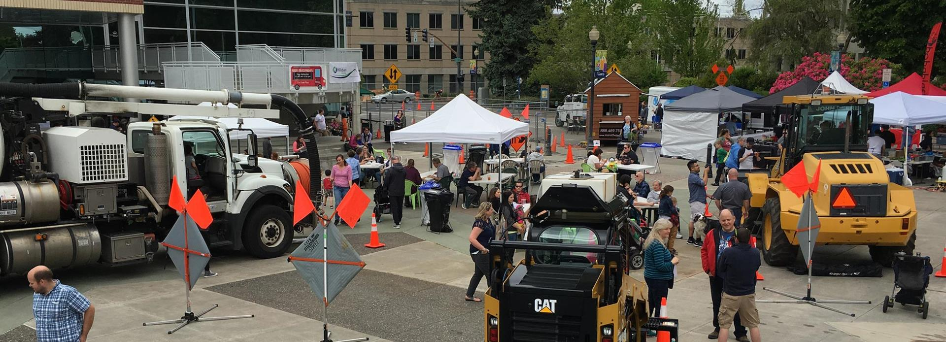 The Civic Center Plaza is pictured with tents, heavy equipment, and many visitors for Public Works Day.