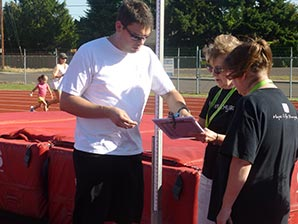 Volunteers review a clipboard at the track.