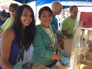 Two young female volunteers smile as they serve popcorn at Celebrate Hillsboro