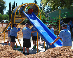 KaBOOM! Volunteers install a slide at McKinney park during a playground build