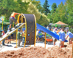 Volunteers construct a playground slide as part of the KaBOOM! Build a Park in Day project.