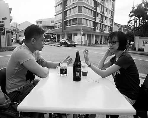 Two friends dine at a sidewalk cafe in an urban setting looking at empty hands that hold invisible cell phones