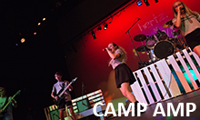 Camp Amp band performing on stage.