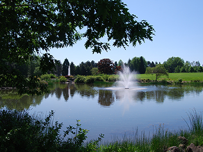 Photo at AmberGlen Park showing one of the fountains and a small lake.