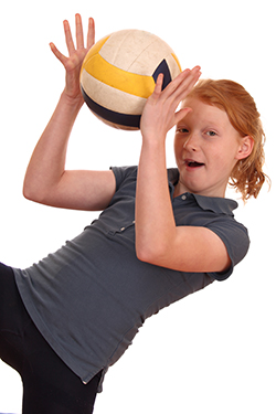 Photo of a young girl holding a volleyball.