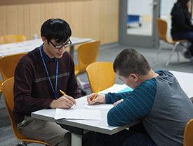 A student and his tutor working together at the library.