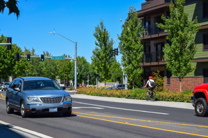 A car and bicycle on the road in Orenco Station