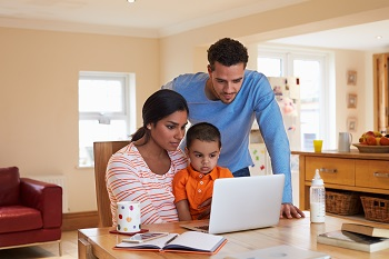 Family with laptop at dining table