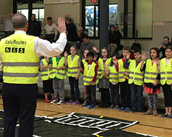 Children wear brightly colored safety vests and practice hand signals at a Safe Routes to School event.