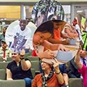 Community members at a City Council meeting hold up large photos reflecting the Cultural Arts initiative