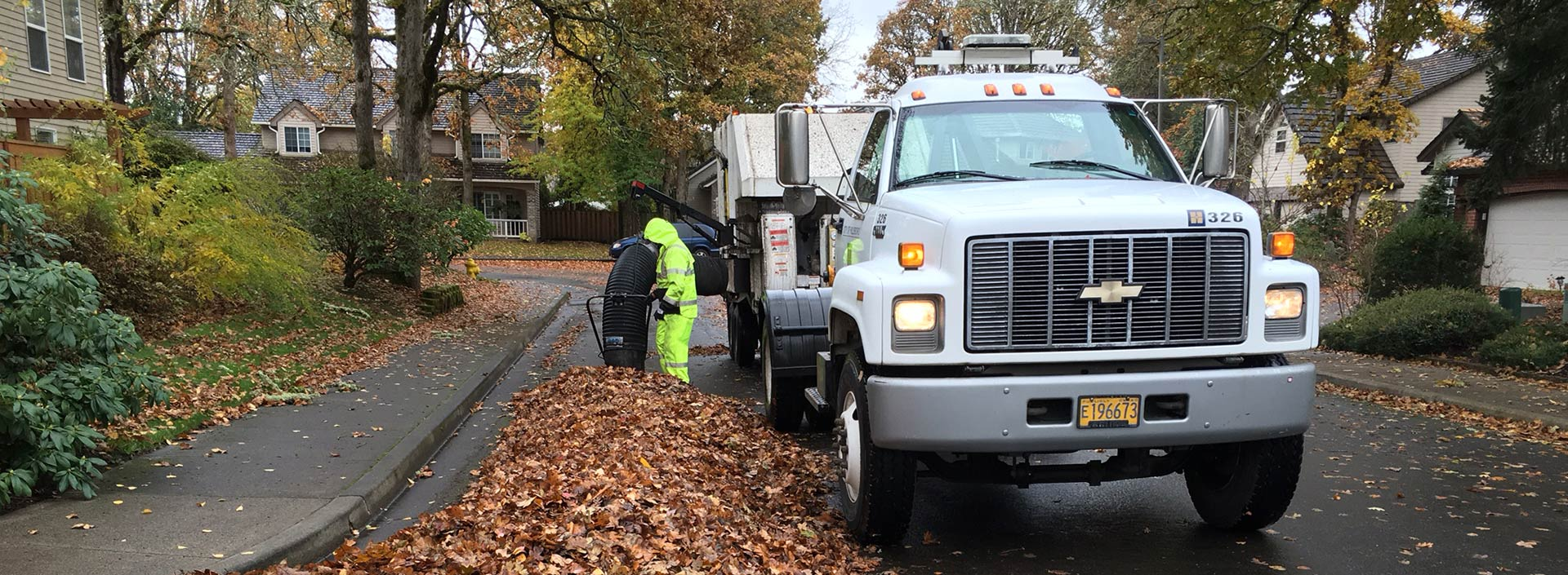 A public works crew member vacuums leaves from a neighborhood street with a large worktruck