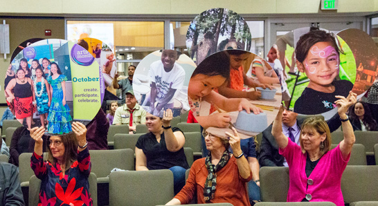 Community members holding up art photos during a City Council meeting.
