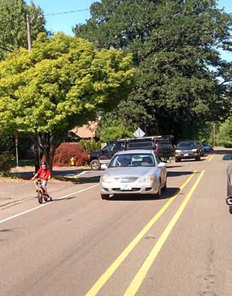 Child biking on Jackson School Road in high traffic