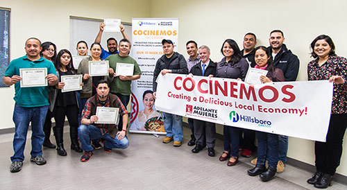Cocinemos graduates pose with their diplomas and a Cocinemos banner that reads: Creating a Delicious Local Economy and features a Adelante Mujeres and City of Hillsboro logos