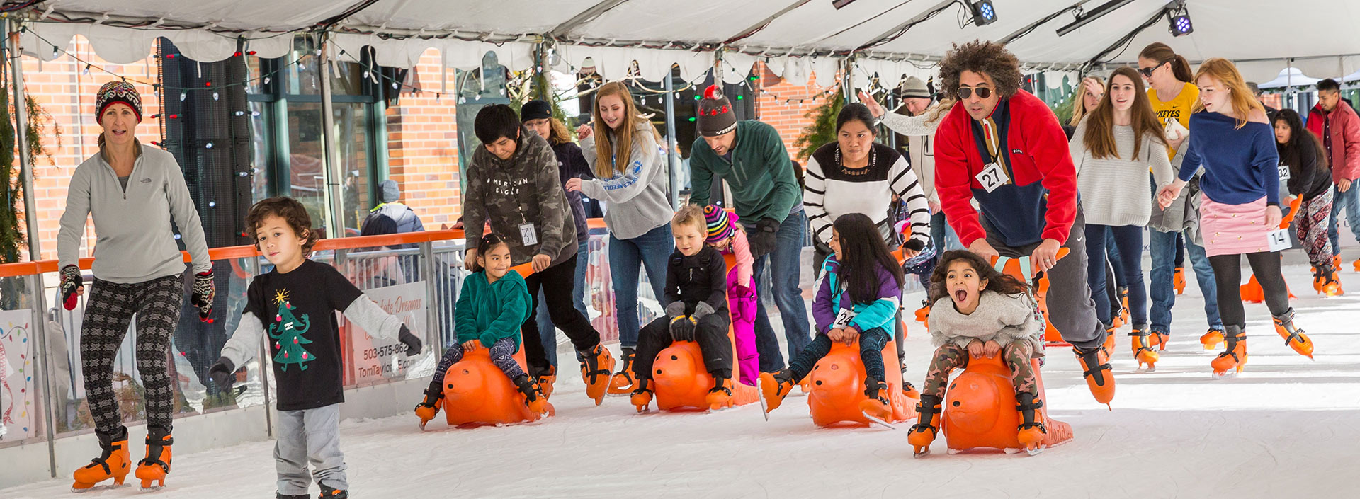 A group of skaters enjoying the ice at Winter Village. Many are pushing young children on bobby ice skating aids.