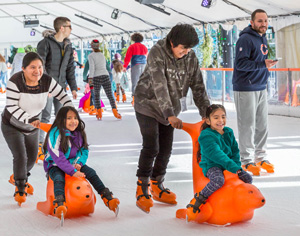 Two children being pushed on ice skating sleds at Winter Village