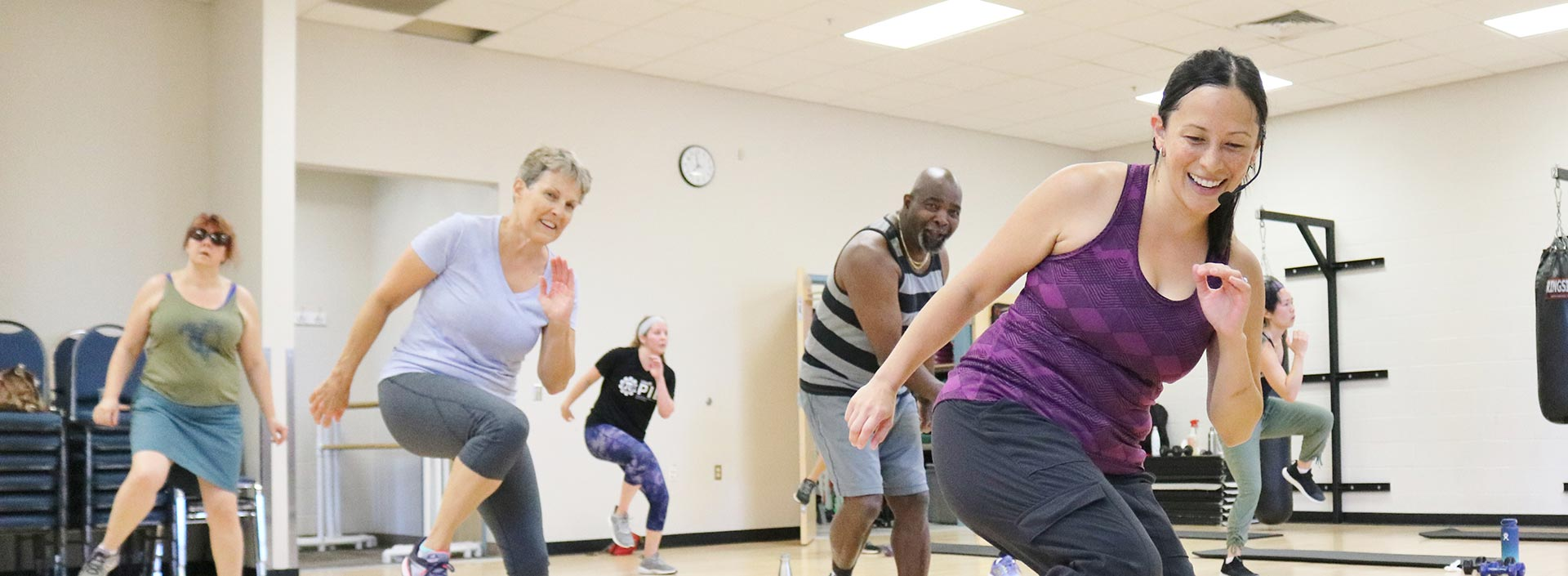 Fitness challenge participants smile during an aerobics class