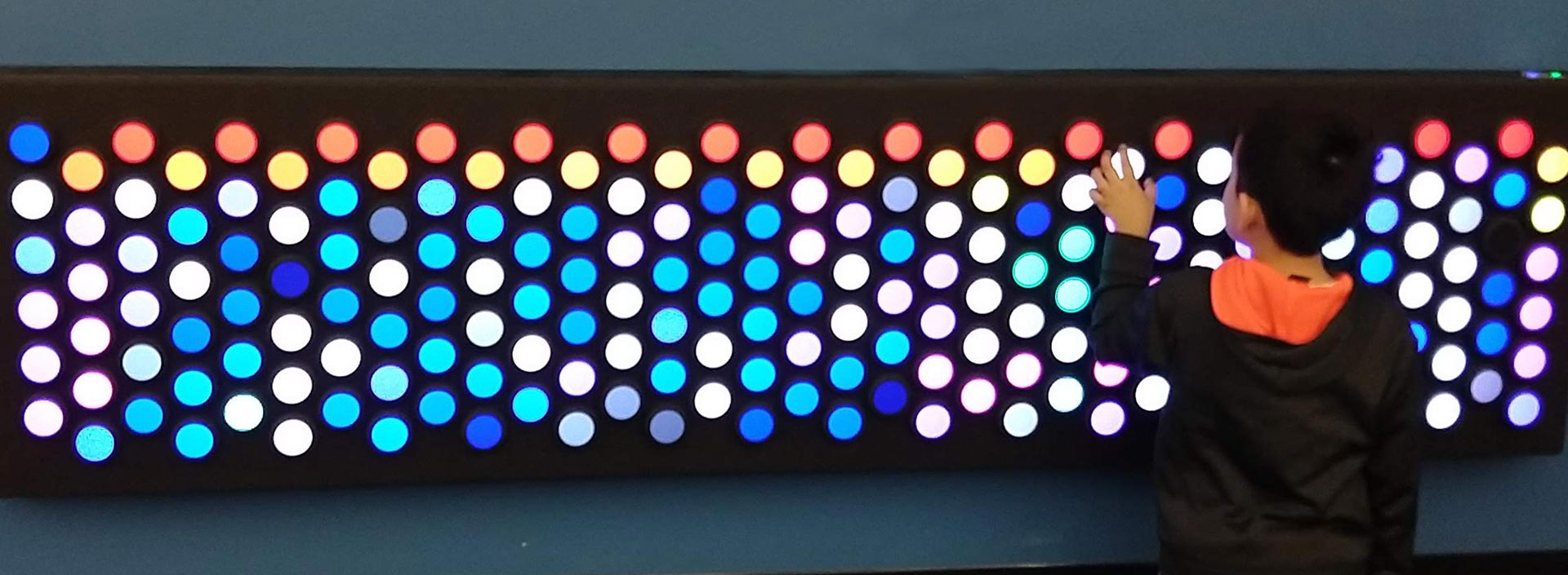A child turns a dial on the EverBright interactive light wall