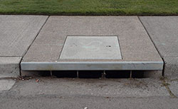 A curb inlet storm drain is a small opening near the edge of the sidewalk and street
