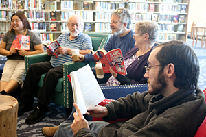Five people discussing a book in a Book Group