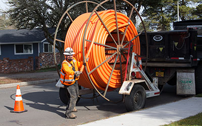 A construction worker pulls orange conduit, or flexible pipe, from a large spool