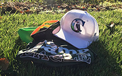 A Camp Eagle hat and sunglasses on the grass on a sunny day