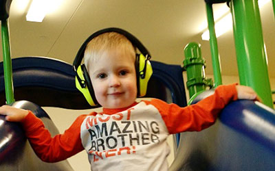A boy wears headphones on a slide during sensory friendly playtime