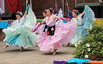 Dancers in traditional extravagant dresses at the El Grito event
