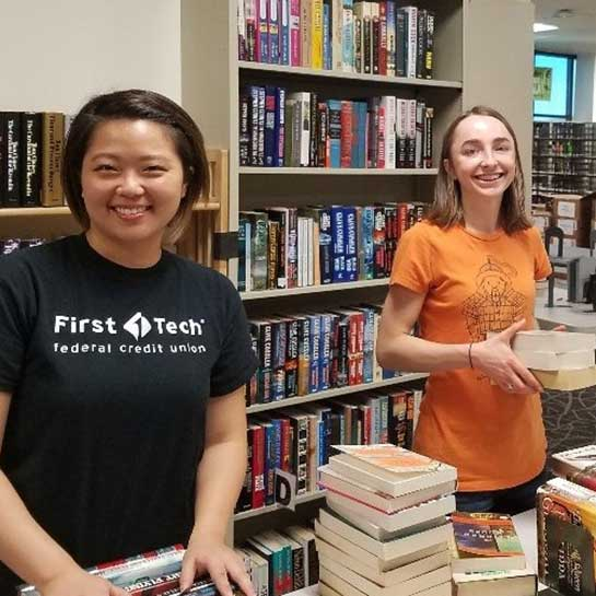 Two-volunteers-with-stacks-of-books
