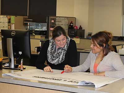 Two female employees look at building plans while working for the City of Hillsboro
