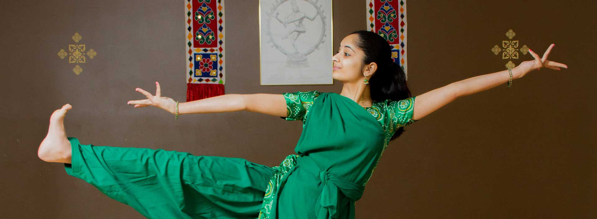A young woman in traditional Indian dress strikes a dance pose