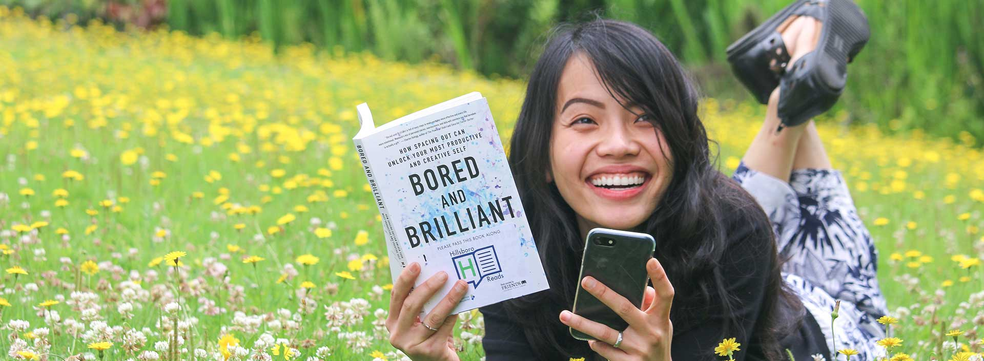A young woman reads Bored and Brilliant by Manoush Zomorodi and holds a cell phone in a field