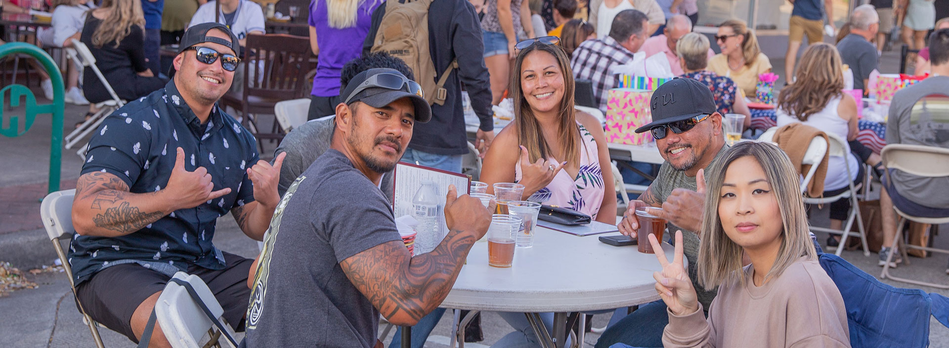 A family greets the camera as they enjoy drinks at an outdoor event