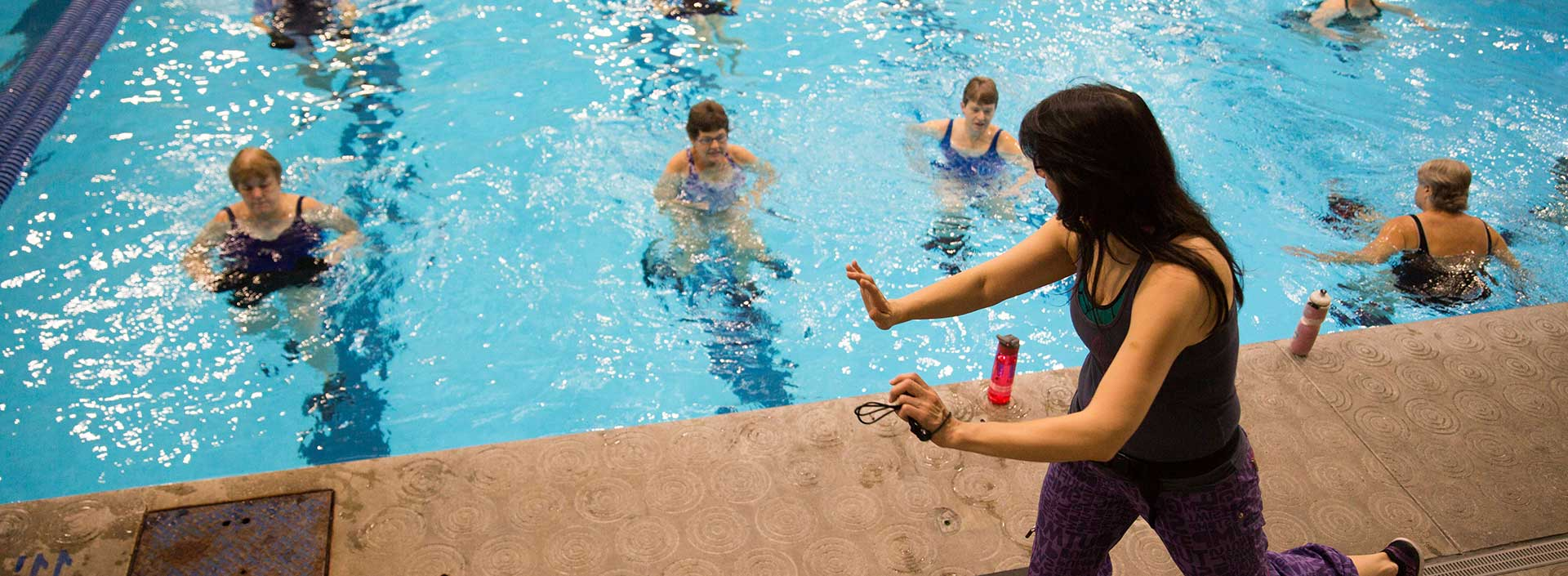 A fitness instructor leads a water aerobics class