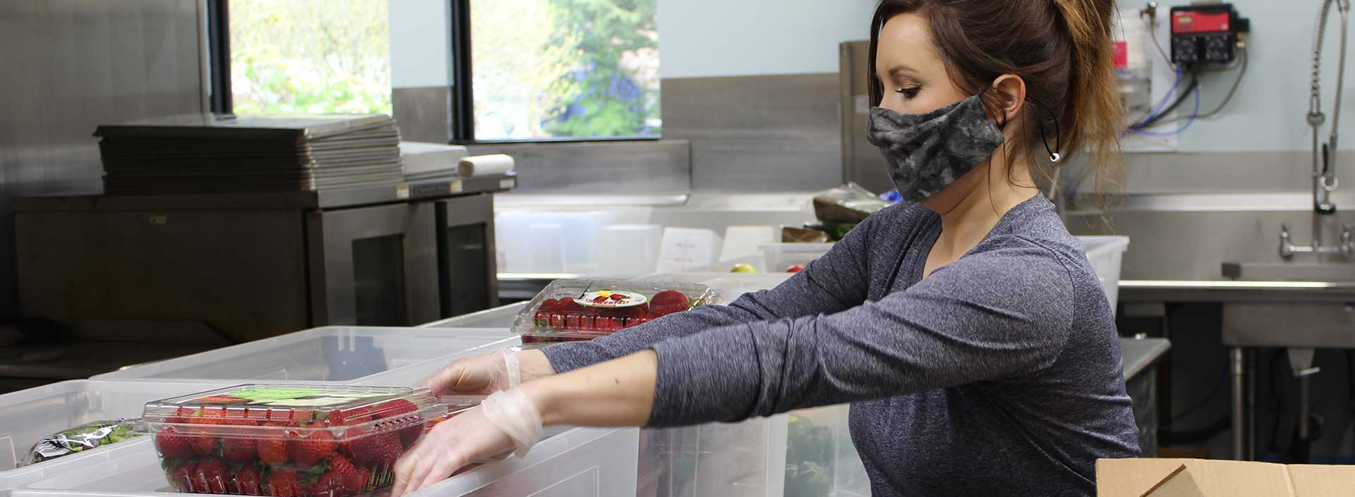 An employee prepares a food delivery in the Senior Center kitchen