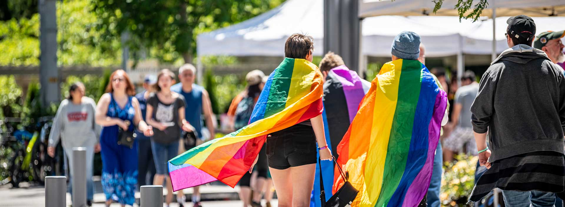 Community members wear rainbow capes at the Pride Month 2019 event