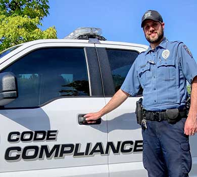 Code Compliance Officer Joey Blanc poses with his vehicle