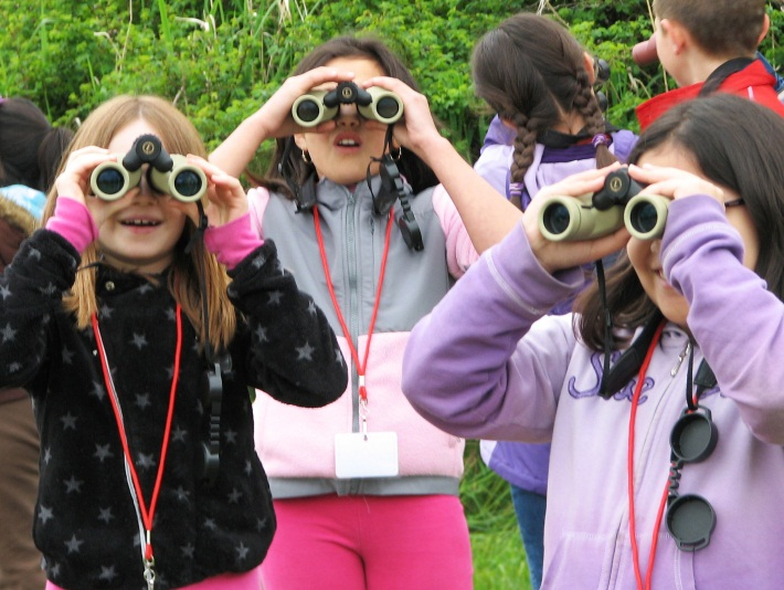 Kids in field experience program looking through binoculars