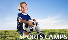 Photo of young boy kneeling on grass holding a soccer ball.