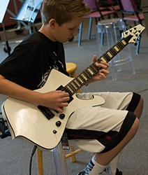 Photo of Camp Amp student playing electric guitar.
