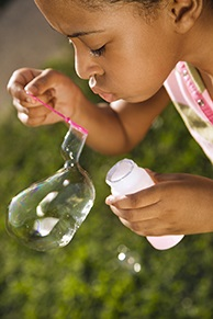 Photo of girl blowing bubbles.