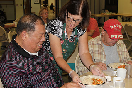 A volunteer serves a meal to two seniors