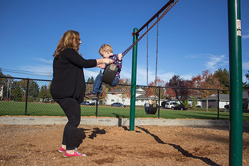Mother and son playing on swings
