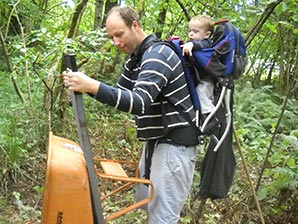 A volunteer dad carries a wheelbarrow while toting his infant son on his back.