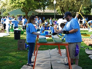 Two volunteers paint playground pieces at a KaBoom! volunteer event.
