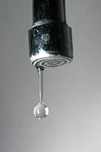 A water drop leaks from a faucet