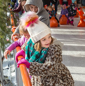 A young girl smiling in her winter hat as she uses the rail for support while ice skating